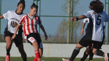 Abril Girandi, la enganche de Racing Club, intenta maniobrar en ataque con el balón ante la férrea marca rival en el Centro Deportivo Trelew.