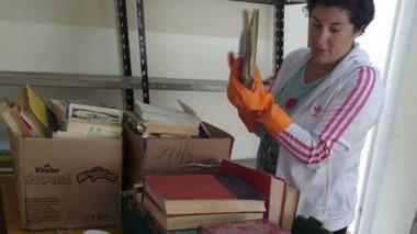Norma Montesinos limpiando y ordenando los libros ya existentes.