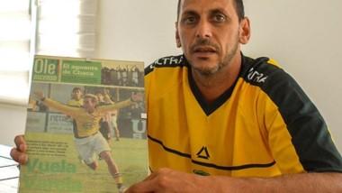 Rubén Darío Ferrer posa con la camiseta de la temporada 2005/06 de Defensa y Justicia de la Primera B Nacional, junto a  recortes periodísticos.