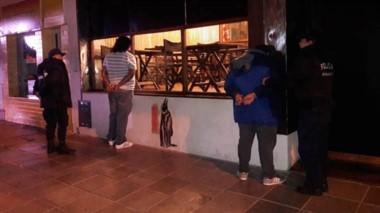 Momentos en que la Policía mantenía reducidos a los violentos sobre la vereda de otro pub de la cuadra.