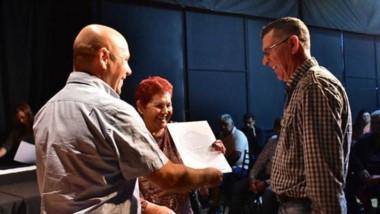 El intendente durante la entrega de los documentos que certifican el título de propiedad de los vecinos.