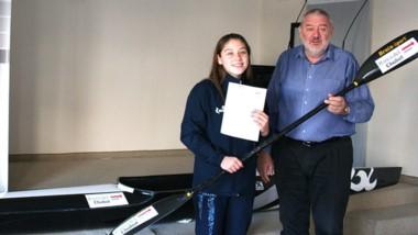 Candela Velázquez recibe un kayak y un remo de manos de Julio Ramírez.
