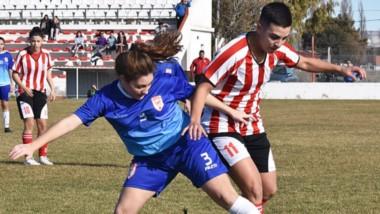 Loreley Bell, de Racing Club, disputa elbalón con Guadalupe Meilipil, defensora de Huracán.