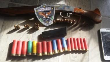 La escopeta y las municiones que fueron incautadas en los registros.