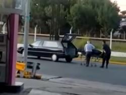 Un policía que se encontraba en la estación de servicio corrió a ayudar al chofer y cargó nuevamente el féretro en el auto.