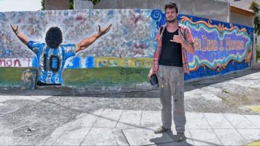 """Mariano Ponte posa junto al mural que pintó por encargo de la peña """"Diego Armando Maradona Eterno""""."""