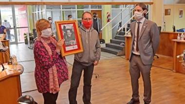 Aplausos. Hilda Fredes y Pablo Bel sostienen el cuadro del militante comunista desaparecido en 1976, segundos antes de colocarlo en el lugar que ocupó Nichols como edil.