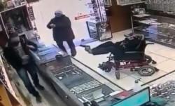 El asaltante manco y en silla de ruedas apunto con el arma al comerciante usando sus pies.
