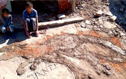 Luciano junto a su hermanito y su obra: el dinosaurio de barro que hizo como tarea de plástica.