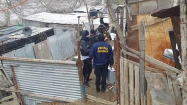 Efectivos policiales de la Brigada de Investigaciones allanando un asentamiento en la zona de Playa 99.