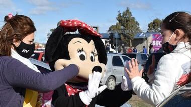 Minnie saluda a una de las niñas y Blancanieves le obsequia caramelos.