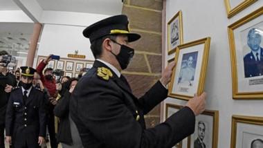 El subjefe de la Policía, Néstor Gómez Ocampo, retirando el cuadro del Juan Luis Ale, condenado por abuso de menores.