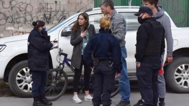 La joven lesionada dialoga con una policía ante la mitada de los ocupantes de la camioneta.