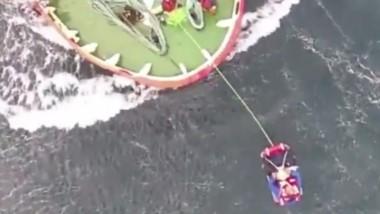 Momento en que se efectúa el rescate del marinero con la canasta sanitaria del helicóptero de la fuerza.