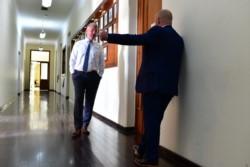 Una charla en el pasillo de los Gobernadores. Sastre habla, Arcioni escucha.