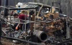 Una mujer busca las pertenencias en los que son los restos de su casa que dejó el terrible incendio.