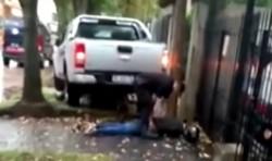 Un policía revisa el cuerpo de uno de los motochorros arrollados por el joven asaltado.