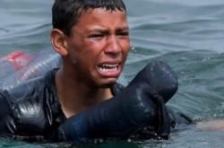 El niño, exhausto y angustiado llegando a la orilla.