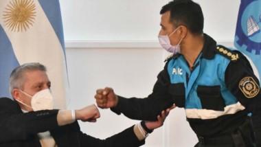 Aporte para la fuerza. El gobernador Mariano Arcioni choca su puño con Miguel Gómez, jefe de Policía.