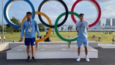 Eulalio Muñoz (derecha) posa con su entrenador Rodrigo Pelaéz junto a los anillos olímpicos en Tokio.