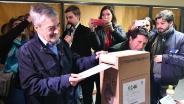 Otros tiempos. Una postal del extinto gobernador Das Neves, rodeado por l a prensa un domingo de voto.