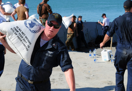 Us navy 080915 n 7955l 072 aviation boatswains mate %28handling%29 3rd class jordan garret carries rice from a landing craft during a humanitarian assistance mission in haiti