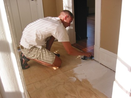 Spreading goop to glue down cement board