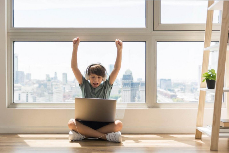 image shows the kid with headphone playing on laptop happily.