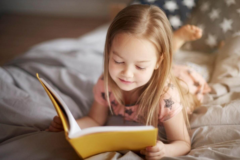 image shows the kid is reading the book.