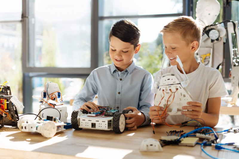 Two kids are playing with robots.