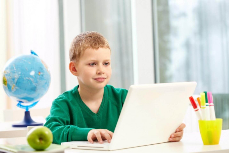 image shows the kid playing on laptop