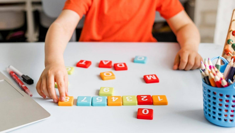 image shows kid playing puzzle.