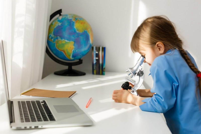 image shows that Kid using telescope for research