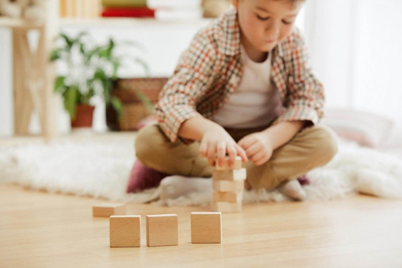 image shows the boy playing with puzzles