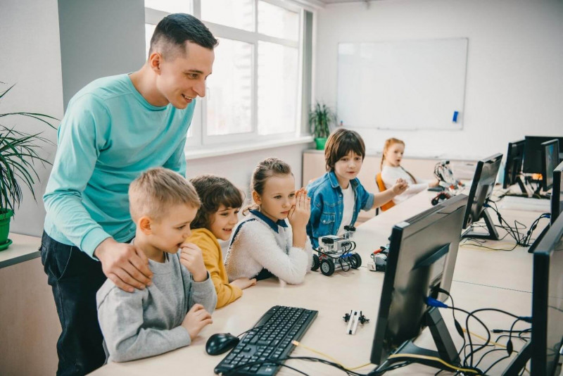 Image shows that kids learning coding with their teacher