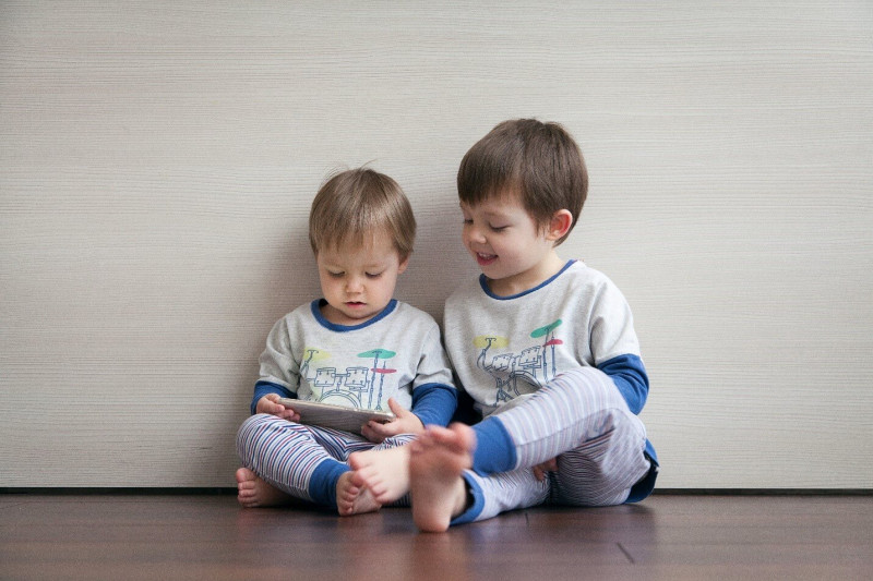 image shows two kids sitting and playing happily