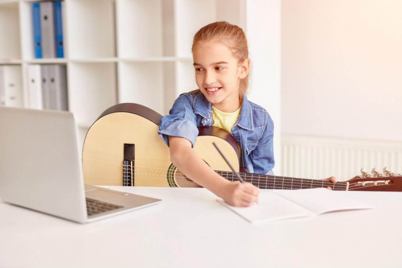 image shows the girl playing with guitar