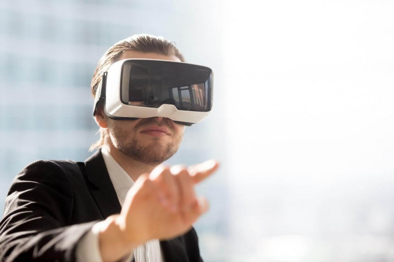 image shows a man with mask using technology