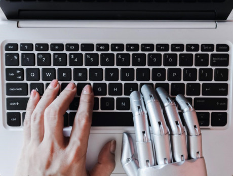 hand of robot and the hand of a human being are typing on laptop.