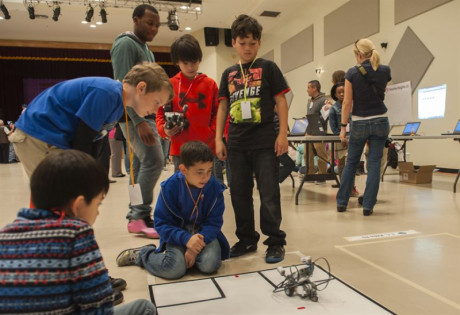 Image to show students during playing with robotics in a summer camp.