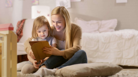 Image shows that the mother teaches her kid on i-pad.