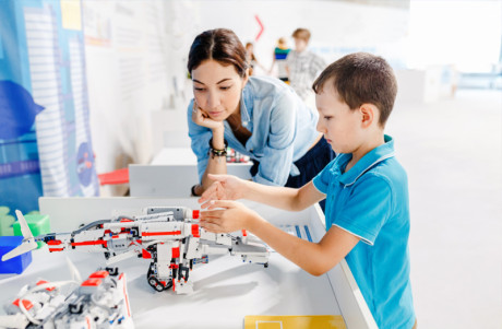 A young kid is collecting lego wedo robot and his mother is standing beside.