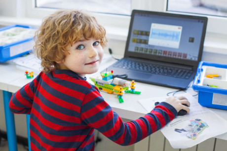 A young kid is studying programming on his laptop.
