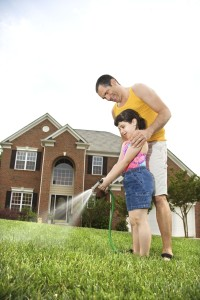 watering yard lawn grass father child daughter rental home lawn care