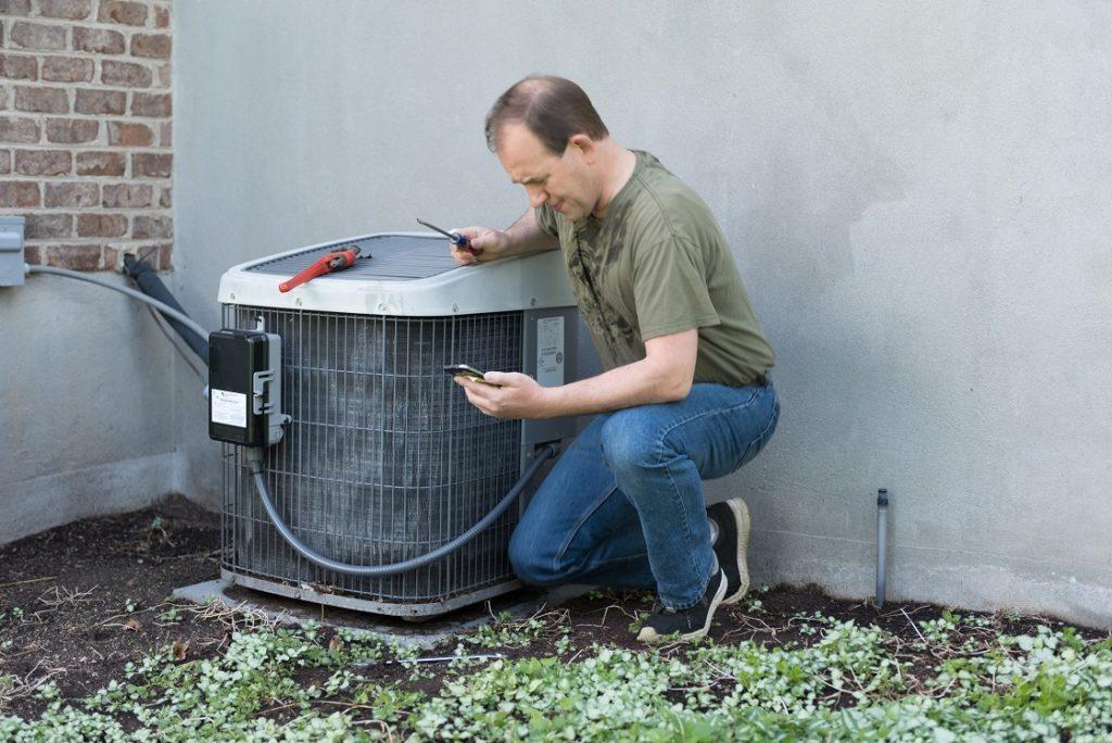 Man repairing AC unit.