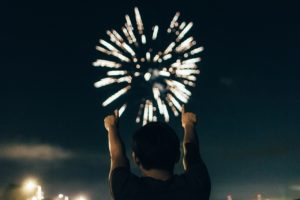 Man in front of fireworks.
