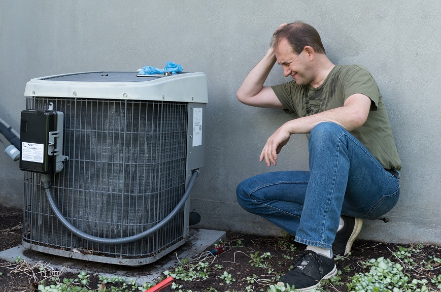 Man frustrated with fixing air conditioner.