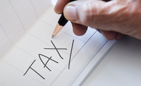 Pen in hand writing tax on paper