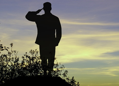 Man saluting on a hill at sunset