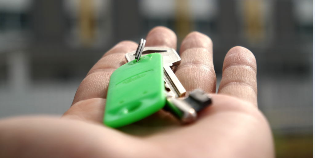 Hand holding keys in front of house